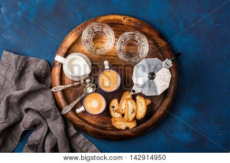 Coffee espresso in cups with italian cantucci, cookies and milk in jug on wooden serving round board over dark blue painted plywood background, top view