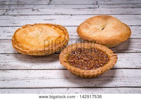 Three miniature pies tarts pecan apple and peach on a white wood beach table .Focus on pecan pie