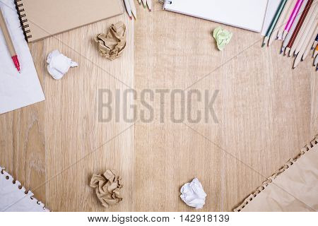 Top view of messy wooden desktop with variety of supplies and crumpled paper balls. Mock up