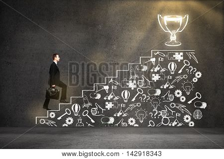 Success concept with businessman climbing abstract ladder and business icons sketch leading to winner's cup on concrete background
