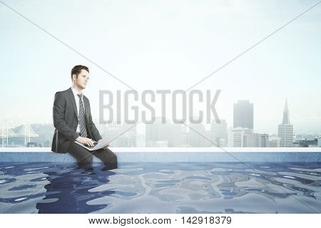 Thoughtful businessman with laptop sitting on the edge of rooftop swimming pool with legs in the water. City background