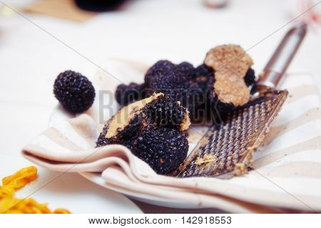 Grated black truffle on plate, close-up, toned image