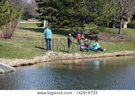 JOLIET, ILLINOIS / UNITED STATES - APRIL 26, 2015: A family enjoys fishing from the side of a small lake in the Wesmere Country Club subdivision of Joliet.