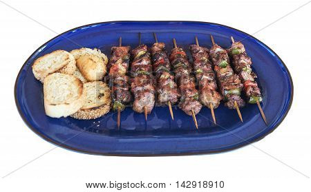 greek kebabs on a blue platter isolated on the white background