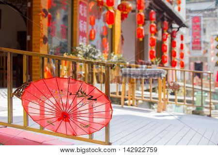 08/10/16 LikengChina - Red Chinese umbrella hanging from a bridge with a restaurant and lantern background of the old town Likeng