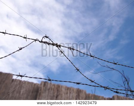 Steel barb wire on a fence under blue sky with clouds Australia 2016