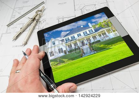 Hand of Architect on Computer Tablet Showing Home Photo Over House Plans, Compass and Ruler.