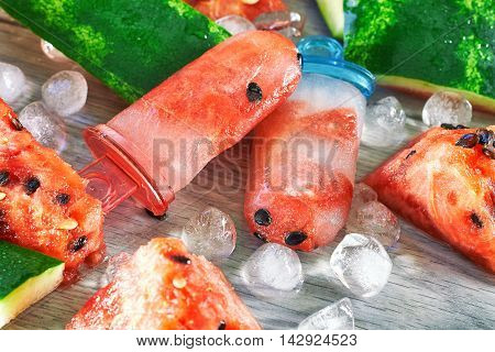 Frozen watermelon popsicles with ice cubes and watermelon slices on grey wooden background. Concept image for summer refreshments