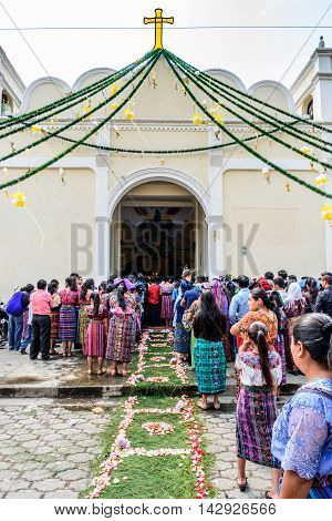 Parramos Guatemala - May 29 2016: Traditionally dressed Mayan woman & men wait outside overflowing church during Corpus Christi mass.