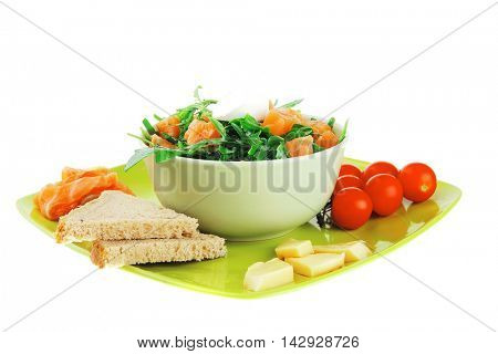 green salad with salmon and tomatoes on plate