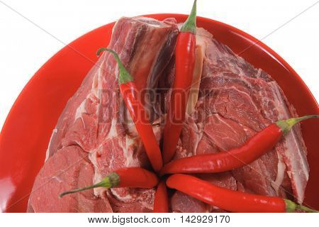 two fresh raw red ribeye beef steak on red plate with hot chili pepper isolated over white background rib eye