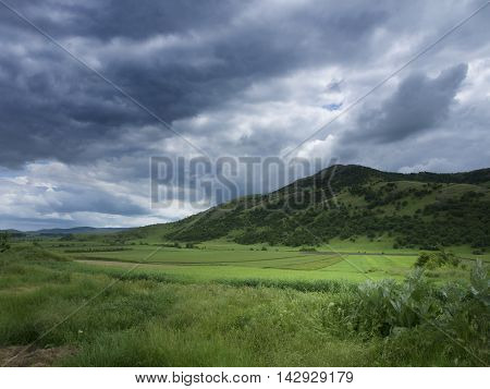 Dramatic skies over Consul hill in Tulcea county, Romania