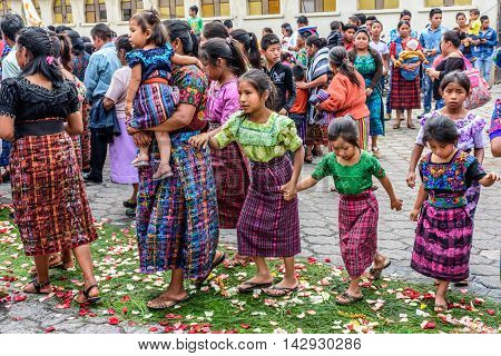 Parramos Guatemala - May 29 2016: Traditionally dressed Mayan women & girls walk over trampled carpet after Corpus Christi procession.