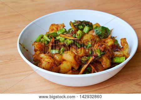 spicy stir fried pork tendon with herb on bowl