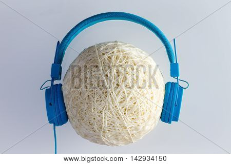 Single ball of wax coated plastic cable or string with large blue headphones over it on gray background
