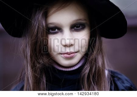 Portrait of a teenage girl in a witch costume. Halloween celebration