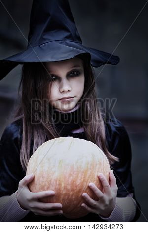 Portrait of a teenage girl in a witch costume with a pumpkin. Halloween celebration