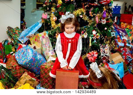 A young girl with a big silver bow and Santa dress stands holding a box in front of a huge Christmas tree and giant pile of presents.