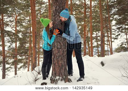 Young happy couple in love in the winter forest. Man and woman outdoors