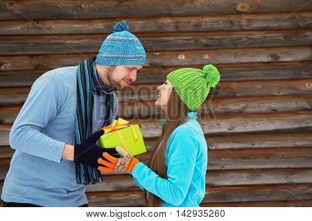 Young happy couple in love outdoors in the winter. a man gives gift to a woman