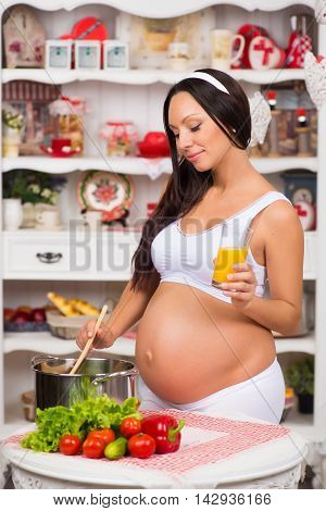 Pregnant woman in the kitchen to cook vegetable soup