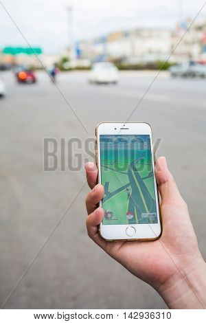 Bangkok Thailand - August 16 2016: Apple iPhone6s held in one hand showing its screen with user plays Pokemon Go a free-to-play augmented reality mobile game developed by Niantic.