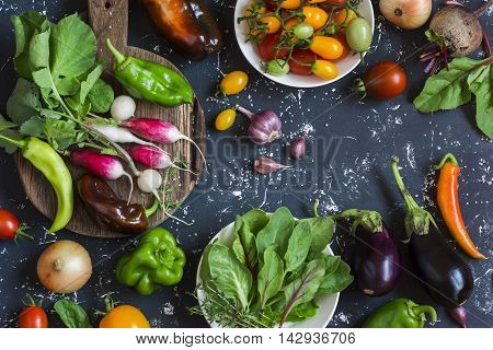 Assortment of fresh vegetables - tomatoes radishes eggplant beets peppers garlic onion spinach. On a dark background top view