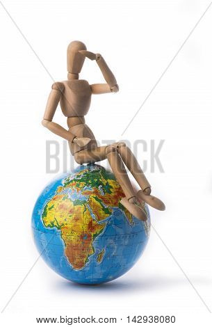 Figurine of a man sitting on a globe and gazes off into the distance