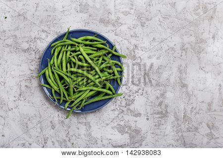 French bean in blue plate on the rough light gray surface with copy space top view