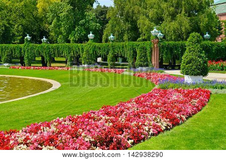 summer park with flower bed and green lawn