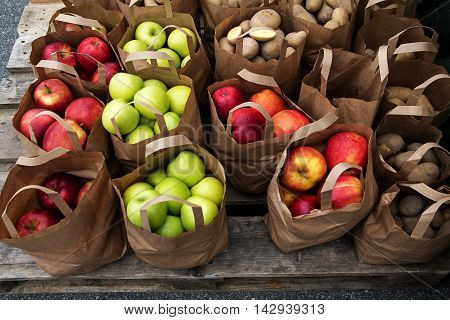 brown paper bags with organic apples and potatoes on the market fresh harvest from the farm selected focus narrow depth of field