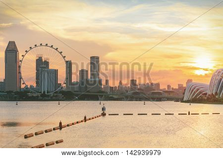 view of central Singapore with water on foreground. Modern city architecture at sunset