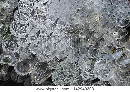 abstract background from different used drinking glasses placed for sale at a flea market selected focus narrow depth of field