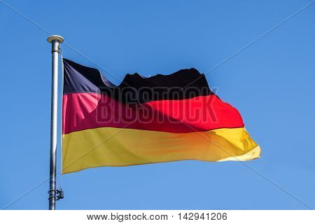 Germany flag fluttering in the wind against the clear blue sky