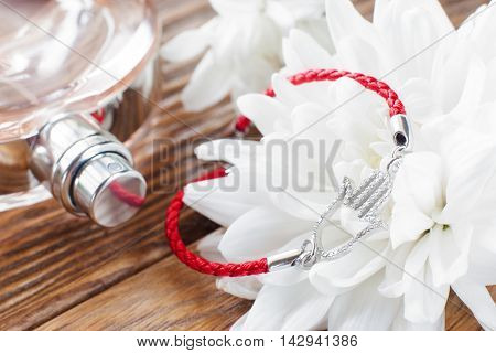 Bracelet on white flower and perfume background. Beautiful soft backdrop with feminine accessories close-up. Romantic composition of female staff