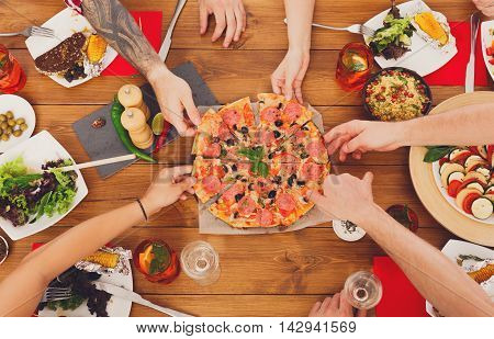 People eat pizza at festive table served for party. Friends celebrate with catering food on wooden table top view. Woman and man's yands take the pieces of italian pizza.
