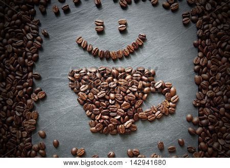Cup of coffee and smiley face from coffee beans. Heap of coffee bean in form of cup on grey stone surface texture. Coffee shop or cafe background. Soft color toning, top view