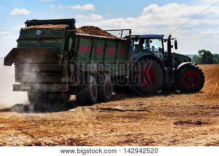 tractor with trailer full of organic fertilizer or manure to the stubble field on a sunny summer day