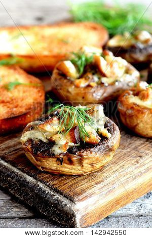 Stuffed mushrooms and fried toasts on a chopping board and wooden table. Baked mushroom caps stuffed with cheese and meat recipe. Closeup