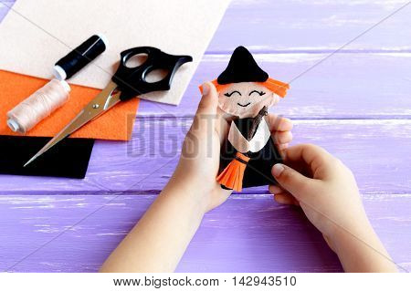 Child holds a Halloween witch doll in his hands and shows it. Scissors, thread, needle, felt on a wooden table. Creative witch DIY for kids. Project for home decor. Halloween crafts inspiration