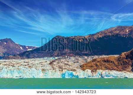 Massive glacier descends into the water.  The picturesque multi-colored shore of Lake Viedma. In the water ice-floes, broken away from a glacier