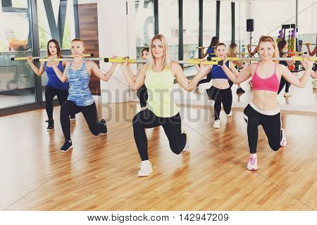 Group of young women in fitness club making exercises. Girls do lunges with barbells. Healthy lifestyle, training with weights.