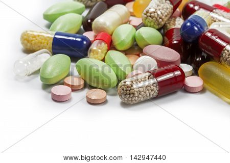 colorful pills and medical capsules as a corner background isolated with shadow on white closeup with selected focus narrow depth of field