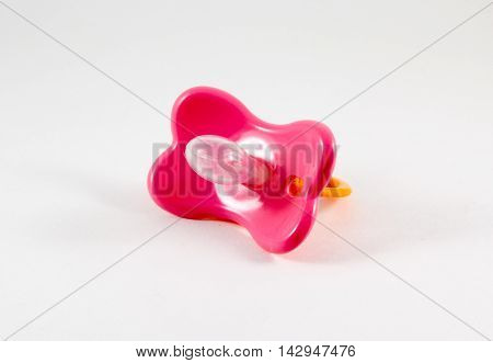 Pink pacifier on a white background .