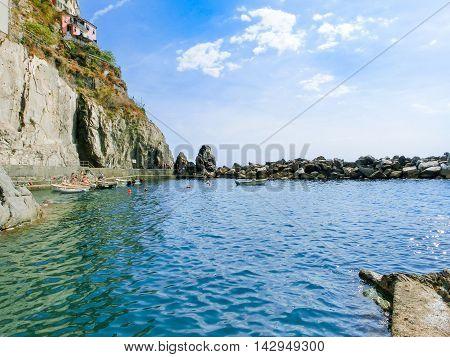 Manarola, Cinque Terre, Italy - September 09, 2015: The boats near a rock at Mediterranean sea at Manarola, Cinque Terre, Italy