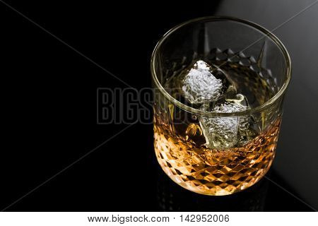 Whiskey With Ice Cubes In Glass On Black Background