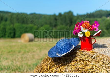 Bouquet garden flowers and summer hat on hay roll in summertime