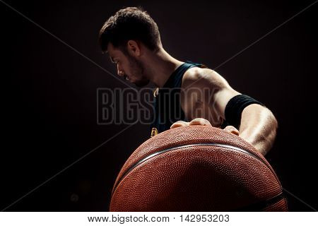 The silhouette view of a basketball player holding basket ball on black background
