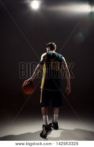 The silhouette back view of a basketball player holding basket ball on black background