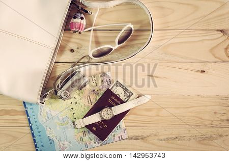 Travel concept with leather handbag sunglasses digital camera world map passport money and wristwatch on wooden table